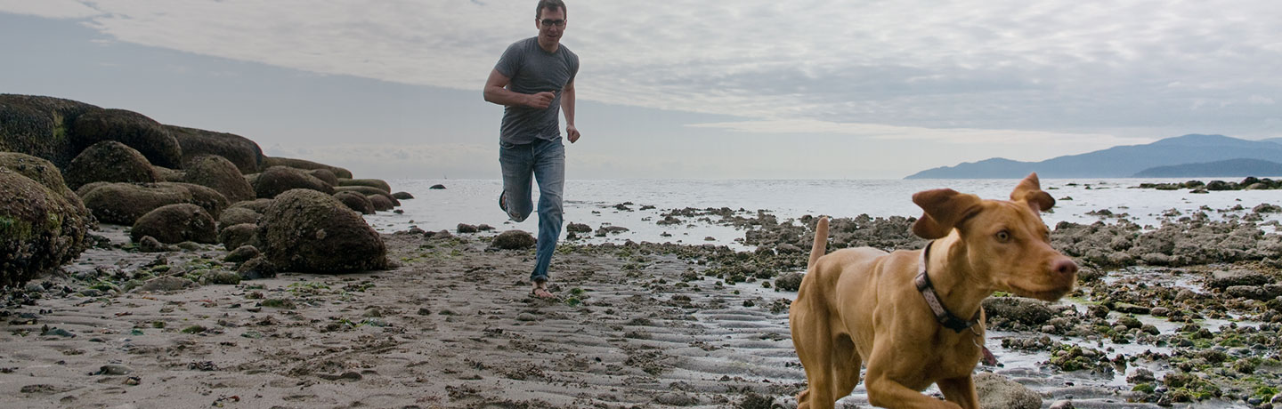 man running on beach with dog